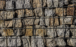 Natural stone wall, versatile in horticulture and slope stabilization; Wire basket filled with broken stones; Buildin  Background. Royalty Free Stock Photo