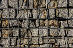 Natural stone wall, versatile in horticulture and slope stabilization; Wire basket filled with broken stones; Buildin  Background. Stock Photo
