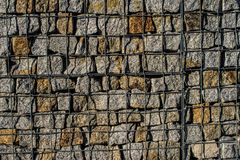 Natural stone wall, versatile in horticulture and slope stabilization; Wire basket filled with broken stones; Buildin  Background. Natural stone wall, versatile Stock Photos