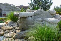 Natural stone waterfall cascade in pond design. Water feature design, two-tiered patio pond built with stone boulders Stock Photo