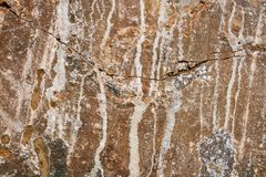 Natural stony grunge brown background with crack and white smudges. Natural stony grunge brown background with uneven wavy crack and vertical white smudges Stock Photo