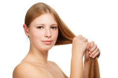 Natural strength. Young beautiful woman with long blond hair holded in hand isolated on white background Royalty Free Stock Photo