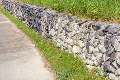 Natural style of exterior stone cement wall beside entrance cement pathway. royalty free stock photos