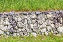 Natural style of exterior stone cement wall in green grass backg. Natural countryside style of exterior stone cement wall in green grass background, strong Stock Photo