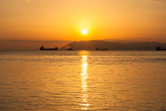Natural summer sea sunset. Silhouettes of ships and strip of land on the horizon. Stock Photography