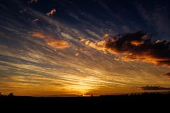 Natural Sunset Sunrise Over Field Or Meadow. Bright Dramatic Sky And Dark Ground. Countryside Landscape Under Scenic Colorful Sky. At Sunset Dawn Sunrise. Sun stock images