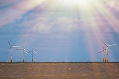 Natural sustainable resources. Bright future of renewable energy. Production. Offshore windfarm on sea horizon with beaming sunlight. Beautiful seascape with Royalty Free Stock Photo
