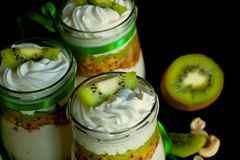 Natural sweet dessert with kiwi and nuts in glass jars on kitchen. Colorful pints for sweet tooth Stock Photo