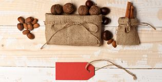 Natural sweets, paper tag or blank price list. Healthy sweets concept. Healthy sweets on light wooden texture background. Bag with walnuts, nuts, cinnamon, top royalty free stock photography