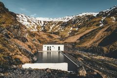 Natural swimming pool Seljavallalaug in iceland with man in water and snowy weather and mountains all around. Sunny stock photos