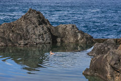 Natural Swimming Pools in Porto Moniz, Madeira, Portugal. A view of the Natural Swimming Pools in Porto Moniz, Madeira, Portugal; a man swimming in one of them stock images