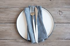 Natural table setting. Plain ceramic plate, linen napkin, cutlery on wooden table. Eco-friendly concept, nordic style stock photo