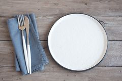 Natural table setting. Plain ceramic plate, linen napkin, cutlery on wooden table. Eco-friendly concept, nordic style royalty free stock images