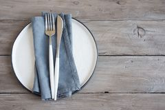 Natural table setting. Plain ceramic plate, linen napkin, cutlery on wooden table. Eco-friendly concept, nordic style royalty free stock image