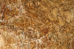 Natural texture photo of nice natural cave with fox-coloured walls and formations of stalagmites in it - Marble Cave, Crimea royalty free stock image