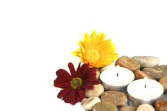 Natural therapy for mind, body and soul. Therapy stones with a yellow and red chrysanthemum each and burning candles. Suitable for a health farm and beauty spa Stock Images