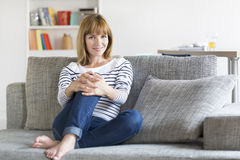 Natural thirty-year-old woman seated on couch in modern home. Portrait of young female at home looking camera on sofa Royalty Free Stock Photo