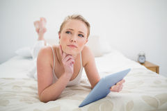 Natural thoughtful blonde lying on bed holding tablet Royalty Free Stock Photo