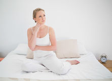 Natural thoughtful blonde sitting in bed Royalty Free Stock Photos