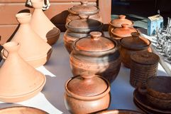 Natural traditional clay pottery beautiful old kitchen appliances, dishes, jugs, vases, pots, mugs. The background royalty free stock image