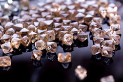 Natural transparent diamonds in macro with yellow reflection on black background Royalty Free Stock Photos