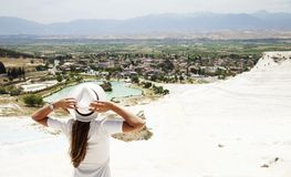 Natural travertine pools and terraces in Pamukkale. Cotton castle in southwestern Turkey, girl in white dress with hat natural poo royalty free stock images