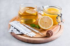 Natural treatment for colds and flu. Lemon, honey, tea, mint and tablets. Natural treatment for colds and flu Royalty Free Stock Photo