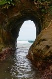 Natural tunnel in the rock dug by sea waves Royalty Free Stock Photo