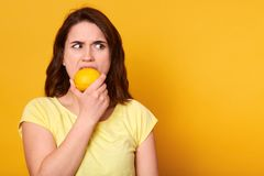 Natural vitamins and healthy food concept. Indoor shot of young brunette woman bits lemon with discontented facial expession,. Looking angrily aside, copy space stock image
