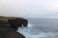 Natural volcanic sea arch on a rocky coastline Royalty Free Stock Photography