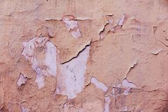 Natural wall with peeling paint. Natural background of old wall with shabby and peeling paint and plaster with cracks and stains of paint royalty free stock photo