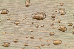 Natural water drops on black wooden Stock Images