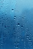Natural water drops on glass. Natural large and fine water drops on blue glass Stock Photography