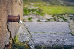 Natural water source with a single water pipe royalty free stock photo
