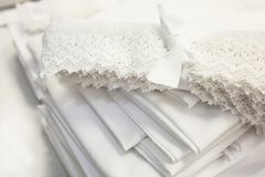 Natural white fabrics for bedding and lace stacked as a fan royalty free stock photography