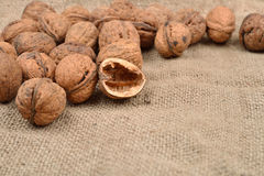 Natural, whole nuts and half empty shell on a jute bag backgroun Royalty Free Stock Photography