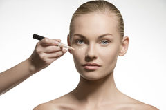 Natural woman applying cosmetics on her visage Royalty Free Stock Images