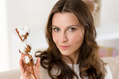 Natural woman with cotton blossom on couch in her living room Royalty Free Stock Photography