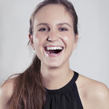 Natural Woman Laughing. Portrait of young woman / girl laughing with gray background Royalty Free Stock Photo