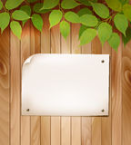 Natural wooden background with leaves and a blank piece of paper Royalty Free Stock Image
