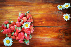 Natural wooden background with strawberries in the shape of a he Royalty Free Stock Images