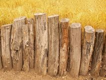 Natural wooden horizontal palisade made from natural trunks, wooden fence between footpath and grass Stock Image