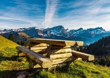 Natural wooden table with benches on the pederstrian path in Alp. S, landscape background, Switzerland Royalty Free Stock Photography