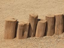 Natural wooden vertical palisade made from natural trunks, wooden fence between footpath and grass Royalty Free Stock Photography