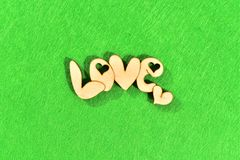 Natural wooden word `love` on green background as grass stock image