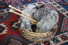 Natural wool and homespun skein in a basket. Raw Natural wool and one homespun skein in a basket on the background of a handwoven woolen carpet Stock Photo
