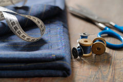 Natural wool, sewing machine bobbin, scissors on a wooden table. Stock Photography