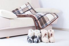 Natural woollen slippers an blanket. Two pair of natural woollen slippers on wooden floor and blanket on the couch Royalty Free Stock Photography