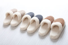 Natural woollen slippers. Three pair of natural woollen slippers on wooden floor Stock Photos