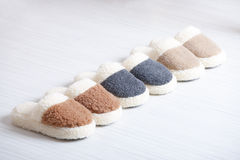 Natural woollen slippers. Three pair of natural woollen slippers on wooden floor Stock Image